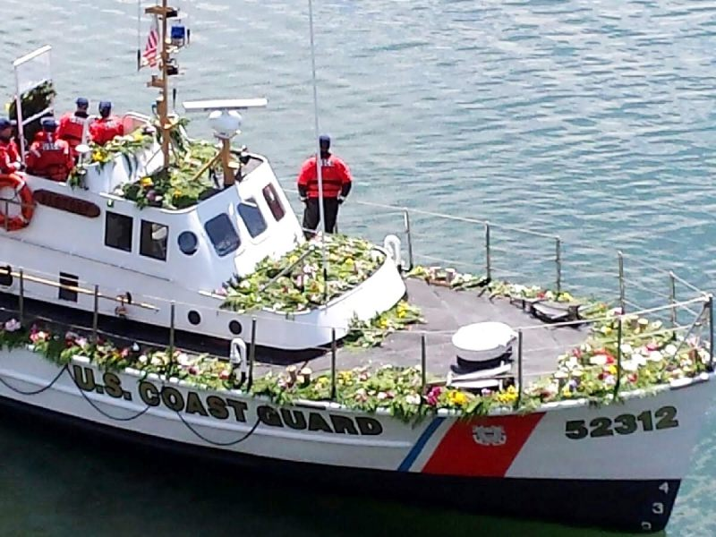 A Coast Guard boat with memorial wreaths