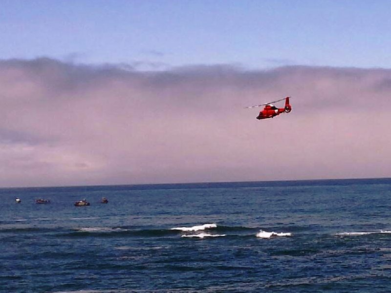 A Coast Guard helicopter drops the first wreath in the Pacific.